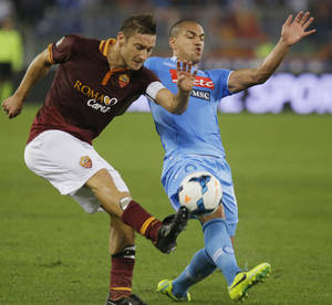 Photo - AS Roma's Francesco Totti, left, and Napoli's Gokhan Inler of Switzerland vie for the ball during a Serie A soccer match between AS Roma and Napoli at Rome's Olympic stadium, Friday, Oct. 18, 2013. (AP Photo/Gregorio Borgia)