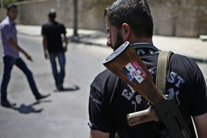 """Photo - FILE - This Aug. 21, 2013 file photo shows a Syrian military soldier holding his AK-47 with a sticker of Syrian President Bashar Assad and Arabic that reads, """"Syria is fine,"""" as he stands guard at a check point in Damascus, Syria. President Barack Obama is asking Congress for $500 million to train and arm vetted members of the Syrian opposition, as the U.S. grapples for a way to stem a civil war that has also fueled the al-Qaida inspired insurgency in neighboring Iraq.  (AP Photo/Hassan Ammar, File)"""
