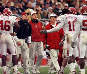 Photo - OU vs. Notre Dame football game: OU head football coach Bob Stoops, (center, red jacket with headphones) walks onto the field to talk with defensive players during a timeout in the 4th qtr. at Notre Dame.