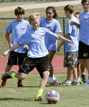 Photo - Preston Taylor, with the HH Ironmen team, makes a kick as teams play kickball to launch an anti-bullying campaign at Heritage Hall Middle School.  Photos by Paul Hellstern, The Oklahoman