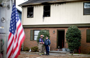 Photo - Rockdale County fire officials stand outside the scene of a house fire that killed four children, including an infant, Wednesday, Jan. 9, 2013, in Conyers, Ga.The fire burned late Tuesday night at a duplex in Conyers, east of Atlanta. Another child, who is 6, was thrown by his mother from a second-floor window, said Glenn Allen, a spokesman for Georgia's fire commissioner. The child injured his shoulder in the fall but survived. The mother was taken to Grady Memorial Hospital in Atlanta with second- and third-degree burns, Allen said. (AP Photo/David Goldman)