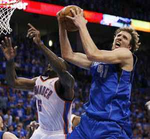 Photo - Dallas' Dirk Nowitzki (41) grabs a rebound next to Oklahoma City's Kendrick Perkins (5) late in the fourth quarter during game one of the first round in the NBA playoffs between the Oklahoma City Thunder and the Dallas Mavericks at Chesapeake Energy Arena in Oklahoma City, Saturday, April 28, 2012. Oklahoma City won, 99-98. Photo by Nate Billings, The Oklahoman