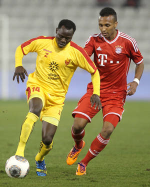 Photo - FILE - In this Jan. 9, 2014, file photo, Bayern Munich's Julian Green, right, of Munich, and Balla Jabir, of Al-Merrikh, challenge for the ball, during their friendly soccer match, at Al-Saad stadium in Doha. Green has joined the U.S. soccer team, a glistening talent still developing, a youngster who grew up in Germany with regular trips to see his father in Florida. He will make his debut for the United States against Mexico on Wednesday, April 2. (AP Photo/Osama Faisal, File)