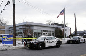 Photo - Police officers stand guard outside the closed post office in Wood-Ridge, N.J., Friday, Jan. 31, 2014. The FBI says a powder mailed to several locations in New York and New Jersey, including at least five hotels near the site of Sunday's Super Bowl appears not to be dangerous. (AP Photo/Mel Evans)