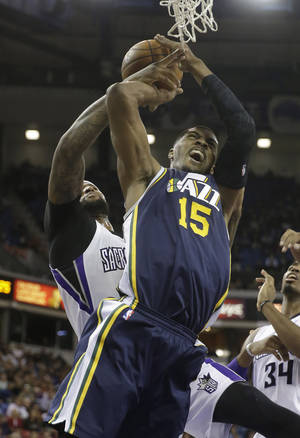 Photo - Utah Jazz forward Derrick Favors, right, is fouled by Sacramento Kings center DeMarcus Cousins during the first quarter of an NBA basketball game in Sacramento, Calif., Wednesday, Dec. 11, 2013. (AP Photo/Rich Pedroncelli)