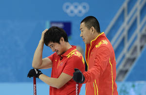 Photo - China's Xu Xiaoming, left, and skip Liu Rui, right, watch as their opponents deliver the rock during the men's curling bronze medal game against Sweden at the 2014 Winter Olympics Friday, Feb. 21, 2014, in Sochi, Russia. (AP Photo/Wong Maye-E)