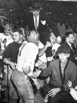 Photo - FILE - In this Nov. 16, 1957, file photo, Notre Dame head coach Terry Brennan is carried off Owen Field by Jim Just (44) and other players following their 7-0 win over Oklahoma in an NCAA college football game in Norman, Okla. Notre Dame's Ron Toth (43) and Jim Colosimo (41) also celebrate the final. That victory ended the Sooners' NCAA-record winning streak at 47 games and came just a season after the Sooners beat the Irish 40-0 in South Bend, still the most lopsided home loss in Notre Dame history. (AP Photo/File) ORG XMIT: NY168