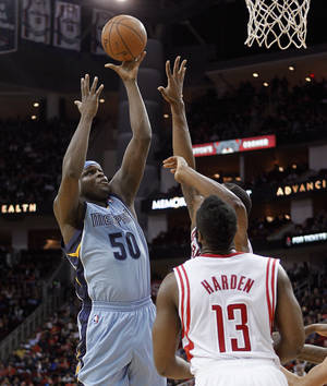 Photo - Memphis Grizzlies forward Zach Randolph, left,  drives to the basket as Houston Rockets guard James Harden (13) watches during the first half of an NBA basketball game Thursday, Dec. 26, 2013, in Houston. (AP Photo/Bob Levey)