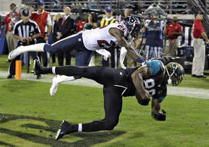Photo - Jacksonville Jaguars tight end Marcedes Lewis (89) pulls in a one-yard touchdown reception in front of Houston Texans cornerback Kareem Jackson (25) during the first quarter of an NFL football game Thursday, Dec. 5, 2013, in Jacksonville, Fla. (AP Photo/Chris O'Meara)