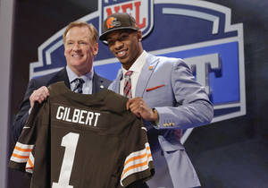 Photo - Oklahoma State cornerback Justin Gilbert, right, poses with NFL commissioner Roger Goodell after being selected by the Cleveland Browns as the eighth pick in the first round of the 2014 NFL Draft, Thursday, May 8, 2014, in New York. (AP Photo/Craig Ruttle)