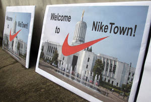 Photo - Signs protesting emergency legislation requested by apparel giant Nike Inc., greet visitors arriving at the Oregon state Capitol in Salem, Ore., on Friday, Dec. 14, 2012. The Legislature is considering a tax deal requested by Nike in exchange for bringing hundreds of new jobs to Oregon. (AP Photo/Jonathan J. Cooper)