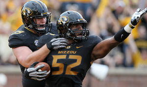 Photo - FILE - In this Sept. 1, 2012, file photo, Missouri linebacker Michael Sam (52) is congratulated by teammate Matt Hoch after returning a fumble seven yards for a touchdown against Southeastern Louisiana during the first quarter, in Columbia, Mo. Michael Sam hopes his ability is all that matters, not his sexual orientation.  Missouri's All-America defensive end came out to the entire country Sunday night, Feb. 9, 2014, and could become the first openly gay player in America's most popular sport. (AP Photo/Chris Lee, St. Louis Post-Dispatch, File)