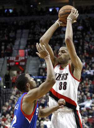 Photo - Portland Trail Blazers forward Nicolas Batum, right, from France, looks to pass inside against Philadelphia 76ers guard Evan Turner during the second half of an NBA basketball game in Portland, Ore., Saturday, Dec. 29, 2012.  Batum led the Trail Blazers with 22 points as they defeated the 76ers 89-85.(AP Photo/Don Ryan)