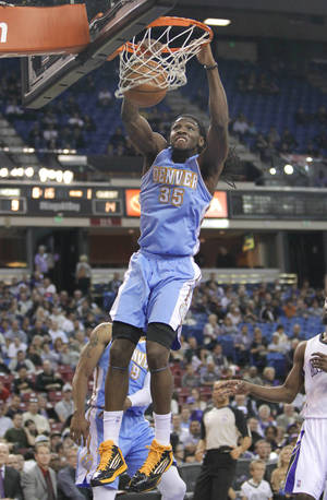 photo - Denver Nuggets forward Kenneth Faried, hangs from the rim after a dunk against the Sacramento Kings during the first quarter of an NBA basketball game in Sacramento, Calif., Tuesday, March 5, 2013. (AP Photo/Rich Pedroncelli)