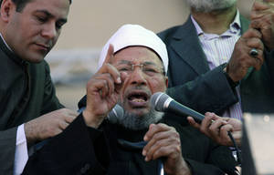 Photo - FILE - In this file photo taken Friday Feb. 18, 2011, Egyptian cleric Sheik Youssef el-Qaradawi speaks to the crowd as he leads Friday prayers in Tahrir Square in Cairo, Egypt. The United Arab Emirates summoned Qatar's ambassador to formally protest the comments of Youssef el-Qaradawi, an outspoken pro-Muslim Brotherhood cleric who criticized the Gulf country's policies toward Islamist groups, the UAE's official news agency reported Sunday, Feb. 2, 2014. (AP Photo/Khalil Hamra, File)