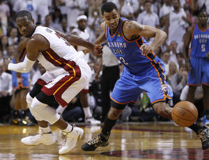 Photo - Miami Heat shooting guard Dwyane Wade (3) and Oklahoma City Thunder shooting guard Thabo Sefolosha (2) of Switzerland go after a loose ball during the second half at Game 3 of the NBA Finals basketball series, Sunday, June 17, 2012, in Miami. Miami won 91-85. (AP Photo/Lynne Sladky) ORG XMIT: NBA155