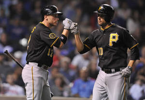 Photo - Pittsburgh Pirates' Jordy Mercer (10) celebrates with teammate Clint Barmes (12) after hitting a solo home run during the third inning of a baseball game against the Chicago Cubs in Chicago, Saturday, June 21, 2014. (AP Photo/Paul Beaty)