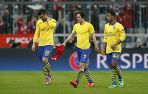 Photo - Arsenal's Oliver Giroud, Tomas Rosicky and Serge Gnabry, from left, leave the pitch after the Champions League round of 16 second leg soccer match between FC Bayern Munich and FC Arsenal in Munich, Germany, Wednesday, March 12, 2014. (AP Photo/Matthias Schrader)