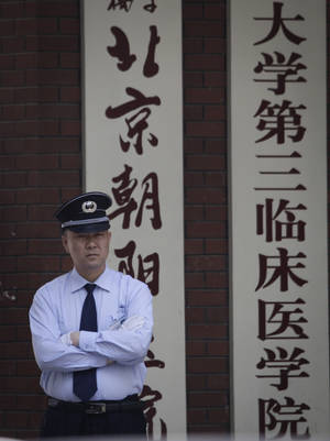 Photo -   A security guard stands in front of the hospital where Chinese legal activist Chen Guangcheng was taken to receive medical care in Beijing, Tuesday, May 8, 2012. Chen who triggered a diplomatic dispute between China and the United States said Monday he is confident that Beijing will hold up its end of a tentative deal to let him study overseas. (AP Photo/Vincent Thian)