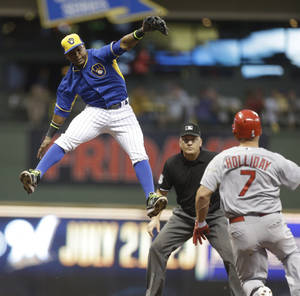 Photo - Milwaukee Brewers' Jean Segura leaps but can't catch a throw on a double by St. Louis Cardinals Matt Holliday (7) during the fourth inning of a baseball game Friday, July 11, 2014, in Milwaukee. (AP Photo/Jeffrey Phelps)