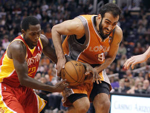 Photo - Phoenix Suns center Hamed Haddadi, right of Iran, is fouled by Houston Rockets guard Patrick Beverley, left, during the second half of an NBA basketball game Saturday, March 9, 2013, in Phoenix. The Suns won 107-105.(AP Photo/Paul Connors)