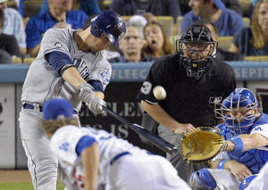 photo -   San Diego Padres' Yasmani Grandal, left, celebrates hits a two-run home run as Los Angeles Dodgers relief pitcher Matt Guerrier, below, looks on along with catcher A.J. Ellis, right, and home plate umpire Derryl Cousins during the eighth inning of their baseball game, Tuesday, Sept. 4, 2012, in Los Angeles. (AP Photo/Mark J. Terrill)
