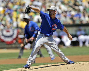 Photo - Chicago Cubs starting pitcher Travis Wood throws to the Oakland Athletics during the first inning of a baseball game on Thursday, July 4, 2013, in Oakland, Calif. (AP Photo/Marcio Jose Sanchez)