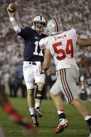 Photo -   Penn State quarterback Matt McGloin (11) throws a touchdown pass under pressure from Ohio State defensive lineman John Simon (54) during the fourth quarter of an NCAA college football game in State College, Pa., Saturday, Oct. 27, 2012. Ohio State won 35-23. (AP Photo/Gene J. Puskar)