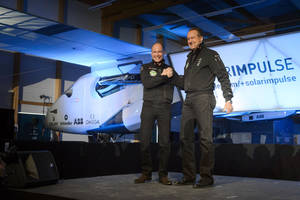 "Photo - Solar Impulse's CEO and pilot Andre Borschberg, right, and Solar Impulse's founder, chairman and pilot Bertrand Piccard, left, shake hands in front of the new experimental aircraft ""Solar Impulse 2"", during the official presentation at the airbase in Payerne, Switzerland, Wednesday, April 9, 2014. The aircraft is the second solar plane of the Solar Impulse project. The Swiss team is planning to complete the first round-the-world solar flight next year with this plane, which they say could remain in the air indefinitely. (AP Photo/Keystone, Laurent Gillieron)"