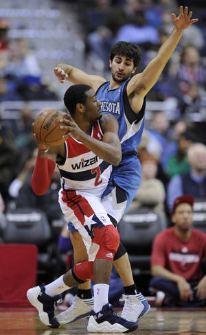 Photo - Washington Wizards guard John Wall (2) tries to get around Minnesota Timberwolves guard Ricky Rubio, of Spain, during the first half of an NBA basketball game on Friday, Jan. 25, 2013, in Washington. (AP Photo/Nick Wass)