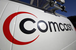 Photo - FILE - This Feb. 11, 2011, file photo, shows the Comcast logo on one of the company's vehicles, in Pittsburgh. Comcast plans to sell some cable systems to competitor Charter Communications Inc., to help Comcast's acquisition of Time Warner Cable clear regulatory hurdles, the company announced Monday, April 28, 2014. (AP Photo/Gene J. Puskar, File)
