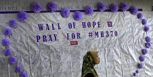 Photo - FILE - In this March 23, 2014 photo, a woman walks past a message board for passengers aboard a missing Malaysia Airlines plane, at a shopping mall in Kuala Lumpur, Malaysia.   With no answers yet in the disappearance of Malaysia Airlines Flight 370, investigators have said they're considering many options: hijacking, sabotage, terrorism or catastrophic equipment failure. Nobody knows if the pilots are heroes who tried to save a crippled airliner or if one collaborated with hijackers or was on a suicide mission. The mystery has raised concerns about whether airlines and governments do enough to make sure that pilots are mentally fit to fly.  (AP Photo/Lai Seng Sin)