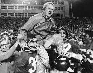 Photo - FILE - In this Dec. 6, 1975, file photo, Arkansas coach Frank Broyles is carried from the field by players Teddy Barnes, left, and Richard LaFargue (52) following his team's 30-6 NCAA college football game victory over Texas A & M in Little Rock, Ark. Broyles, now 89, is Arkansas' most successful football coach and unquestioned patriarch of athletics still comes into the office every day. (AP Photo/Ferd Kaufman, File)