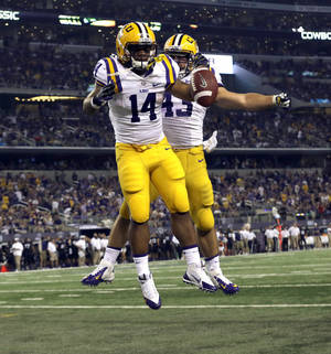 Photo - LSU running back Terrence Magee (14) celebrates scoring a touchdown with teammate Connor Neighbors (43) during the second half of an NCAA college football game against the TCU, Saturday, Aug. 31, 2013, in Arlington, Texas. (AP Photo/LM Otero)