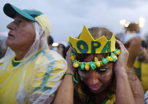 Photo - Brazil soccer fans wearing their team's colors Brazilian react as they watche their team play Germany in a World Cup semifinal game via live telecast inside the FIFA Fan Fest area on Copacabana beach in Rio de Janeiro, Brazil, Tuesday, July 8, 2014. Germany handed Brazil its heaviest World Cup loss ever with an astounding 7-1 rout in the semifinals that stunned the host nation. (AP Photo/Leo Correa)