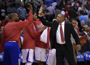 Photo - Los Angeles Clippers head coach Doc Rivers, right, congratulates members of his team during the second half in Game 5 of an opening-round NBA basketball playoff series against the Golden State Warriors, Tuesday, April 29, 2014, in Los Angeles. The Clippers won 113-103. (AP Photo)