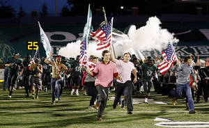 Photo -  Students lead the Edmond Santa Fe Wolves as they take the field before a high school football game between Edmond Santa Fe and Norman at Wantland Stadium in Edmond. Photo by Nate Billings, The Oklahoman Archives  <strong>NATE BILLINGS -   </strong>