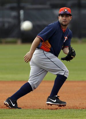 Photo - Houston Astros' Jose Altuve keeps his eye on the ball as he moves in position during a spring training baseball workout, Friday, Feb. 21, 2014, in Kissimmee, Fla. (AP Photo/Alex Brandon)