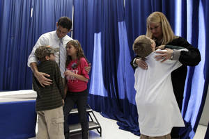 Photo -   Republican vice presidential candidate, Rep. Paul Ryan, R-Wis., and his wife Janna talk to their children, from left, Sam, Liza and Charlie backstage before a campaign event, Sunday, Nov. 4, 2012, in Mansfield, Ohio. (AP Photo/Mary Altaffer)