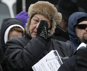 Photo - A unidentified woman wipes her face as she reacts during ceremonies held to unveil plans for a permanent memorial on the site of The Station nightclub fire, Sunday, Feb. 17, 2013, in West Warwick, R.I. The 2003 blaze, which broke out when pyrotechnics for the rock band Great White ignited flammable packing foam that had been installed inside the club as soundproofing, took the lives of 100 people. (AP Photo/Steven Senne)