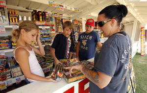 Brook Rankin, 12, Brock Lunsford, 13, and Brandon Rankin, 14, sell fireworks to Kristy Beitler at a fireworks stand on State Highway 9, just west of Interstate 35. PHOTO BY STEVE SISNEY, THE OKLAHOMAN