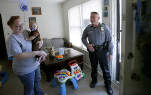 photo - Oklahoma City police Sgt. Philip Paz talks with Misty Combs as he holds her son, Dylan Combs, 9 months.  Photo by Sarah Phipps, The Oklahoman
