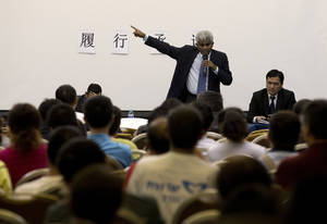 "Photo - Bala Chandran Tharman, deputy chief of mission at the Malaysian embassy in Beijing speaks to relatives of Chinese passengers onboard the Malaysia Airlines MH370 during a briefing at a hotel in Beijing, China Saturday, April 26, 2014. A number of Chinese relatives still aren't accepting the theory that the plane crashed in the Indian Ocean. They're insisting that Malaysian officials haven't told them the truth. The Chinese characters on the wall reads: ""Meet the commitment."" (AP Photo/Andy Wong)"