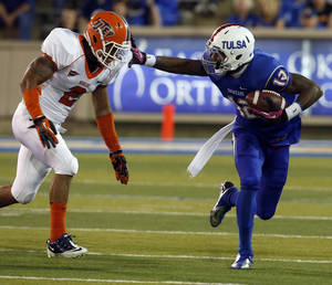 photo -   Tulsa's Jordan James looks for room as UTEP's (2) DeShawn Grayson pursues during first half of an NCAA college football game in Tulsa, Okla., Thursday Oct 11, 2012. (AP Photo/Tulsa World, Tom Gilbert)
