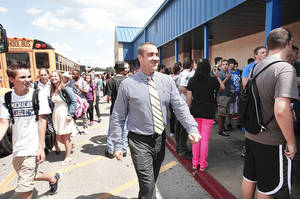 Photo - David Reid walks among students waiting to get on buses at the end of the school day. Tuesday was Reid's first day as principal of Choctaw High School. Photo by Jim Beckel, The Oklahoman