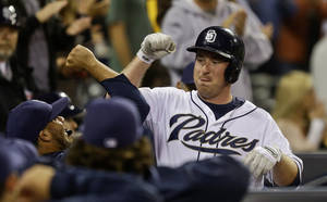 Photo - San Diego Padres' Jedd Gyorko, right, smashes forearms with Rene Rivera after Gyorko's second home run of the game against the Chicago Cubs in the eighth inning of a baseball game Friday, Aug. 23, 2013, in San Diego. (AP Photo/Lenny Ignelzi)