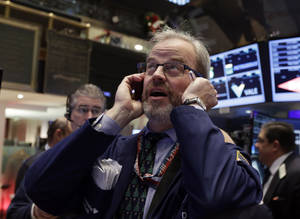 Photo - FILE - In this Wednesday, Dec. 18, 2013, file photo, Trader David O'Day uses his mobile phone as he works on the floor of the New York Stock Exchange. (AP Photo/Richard Drew, File)