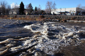 Photo - People come out to watch the surging Truckee River, in downtown Reno, Nev., on Sunday, Dec. 2, 2012, as a heavy, wet storm hit the Northern Nevada region. The storm delivered more snow and less rain than forecast, blunting the flood danger. (AP Photo/Cathleen Allison)