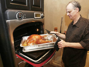 photo - Claude Rappaport removes a turkey from his TurboChef oven after cooking for 39 minutes at his store, Culinary Kitchen. Claude, Lindy and Lori Rappaport, with help from their friend Clayton Bahr, will be cooking as many as 100 turkeys using the latest technology. Photo By Paul Hellstern, The Oklahoman