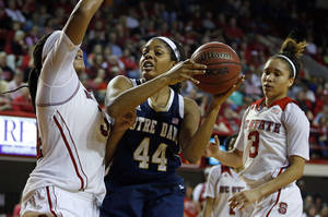 Photo - Notre Dame 's Ariel Braker (44) battles with North Carolina State 's Markeisha Gatling, left, with NC State's Miah Spencer (3) looking on during the second half of an NCAA college basketball game in Raleigh, N.C., Sunday, March 2, 2014. Notre Dame won 84-60. (AP Photo/Karl B DeBlaker)